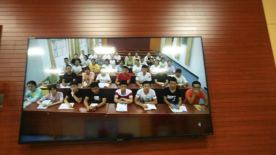 卫星课堂上的孩子们,外教通过屏幕和学生互动。