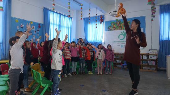 早教项目课堂活动场景:在儿歌《猴子》里孩子们随着老师和节奏一起爬树。
