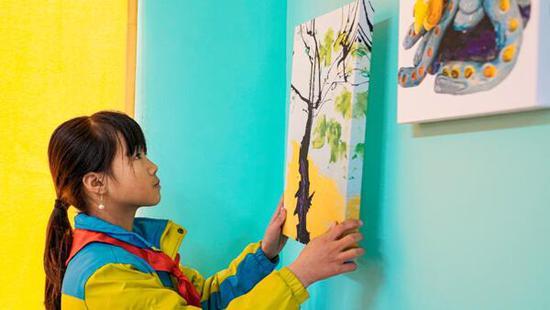 山区小朋友利用城市儿童创作的环保画作装饰图书馆