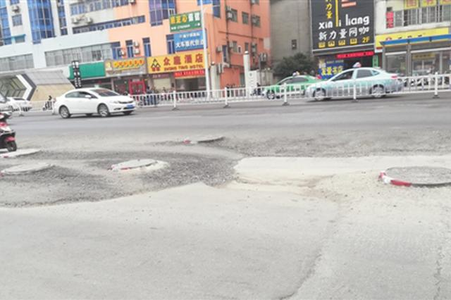 友爱明秀路地铁口道路坑洼:400米辅道有近10个井盖