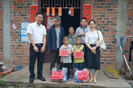圖為:市福彩中心工作人員為孤兒家庭送慰問金和慰問品