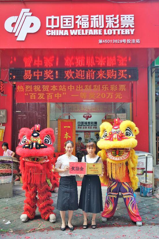 图为:南宁福彩工作人员为中奖的投注站业主(右)颁发牌匾和奖励金