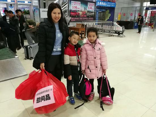 赴深务工者带着孩子,拿着新春慰问口准备登上开往深圳的爱心大巴