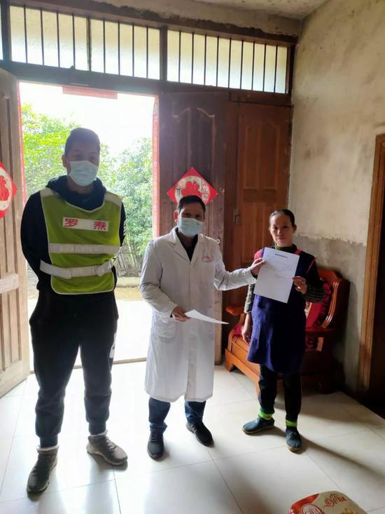 羅燾(左一)和村醫陳立德上門上門指導需按規定進行隔離的群眾簽訂《自我隔離承諾書》