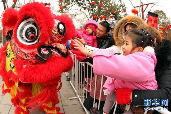 2月7日,河南许昌,人们在灞陵桥景区新春大庙会上观看舞狮表演。