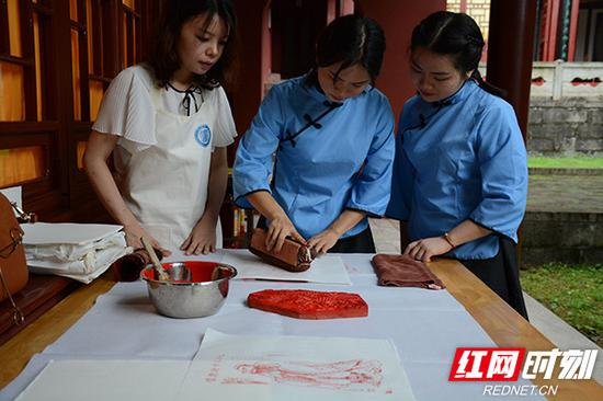 来自湖南大学的在校学生在岳麓书院体验雕版印刷的魅力。