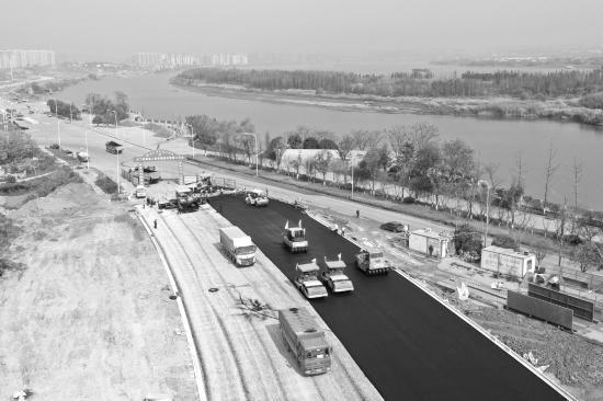 12月9日,湘江西岸堤防整治道路工程,道路五标(督抚路至巴溪大道路)段启动沥青摊铺工作。图/李俐娟