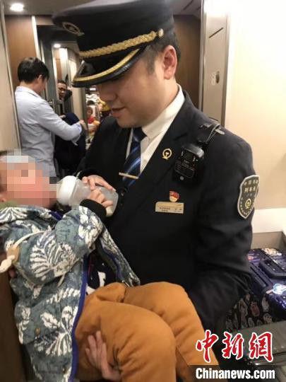 小孩在列车工作人员怀中喝牛奶。长沙客运段供图