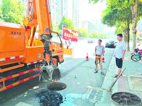 雨污井抓斗车正在南湖大道井盖前进行清淤作业。 谭振华 摄