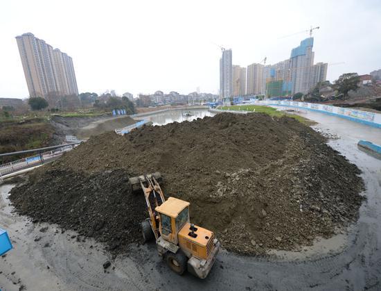 1月7日,在王家河水环境综合治理工程项目部内,推土机将压滤过后的泥饼统一堆放。新华社发(陈振海摄)