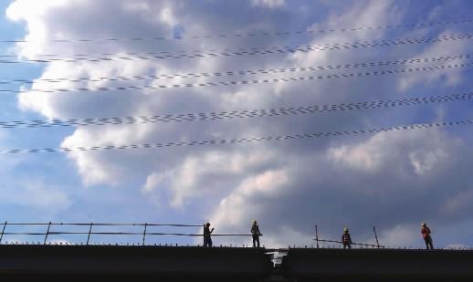 7月4日,长沙市湘府路上,建筑工人在烈日下施工,与蓝天白云构成一幅风景。当天,省气象台发布高温黄色预警,晴热高温天气持续,最高气温达36℃(大图,记者郭立亮摄)。为确保交通安全、防止道路周边植物发生高温热害,7月4日,桂阳县利用雾炮车喷洒水雾,以达到抑尘降温效果(小图,欧阳常海摄)。