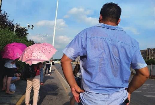 7月4日,长沙市湘府西路上,市民在烈日下等公交车,身上汗流浃背。当天,省气象台发布高温黄色预警,晴热高温天气持续,最高气温达36℃。记者 郭立亮 摄