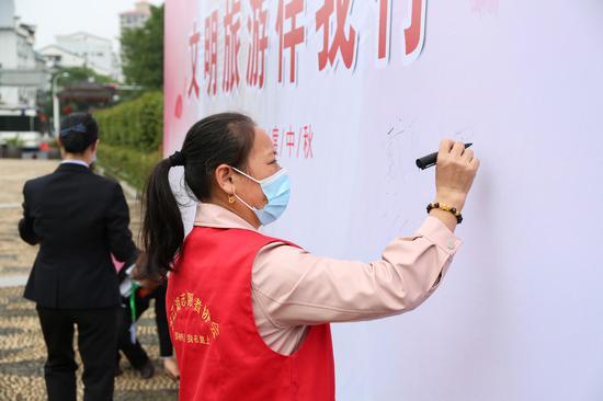 志愿者在签名墙上签名。
