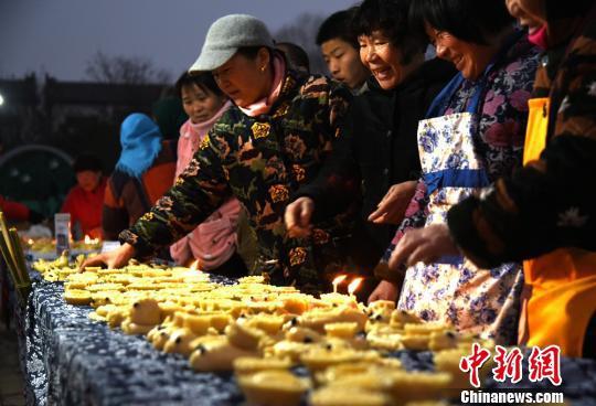 """马庄村150余面灯""""匠人""""互相点评新出锅的面灯。 朱志庚 摄"""