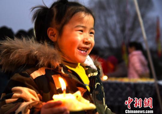 """小孩子端着寓意吉祥幸福的面灯,欢快地绕场""""送福""""。 朱志庚 摄"""