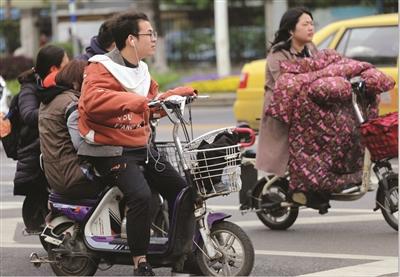 """南京气温""""跳水""""11℃,出行的市民重新穿上了厚衣、厚裤。   新华报业视觉中心记者 宋宁 摄"""