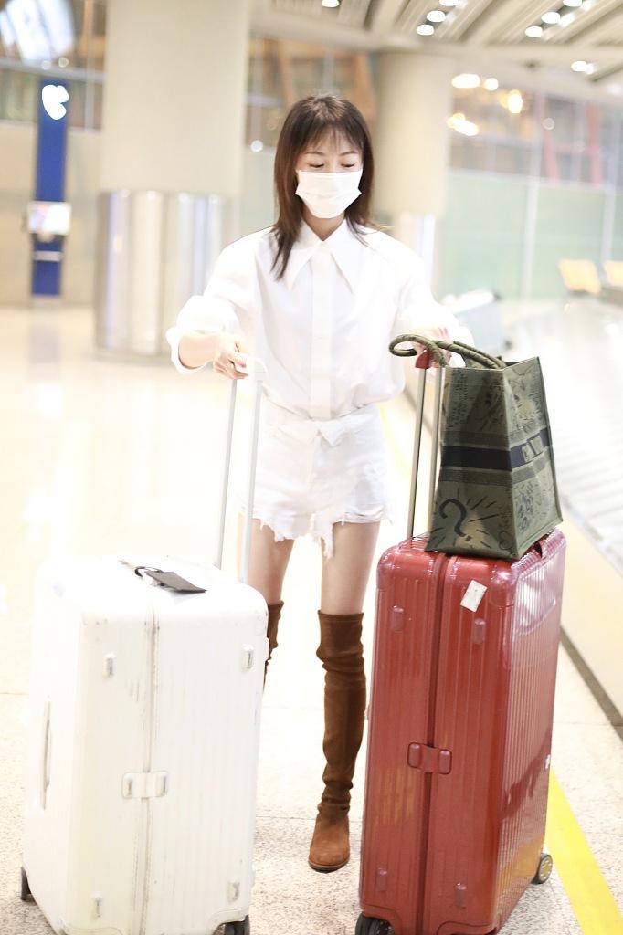 吴谨言穿长筒靴秀漫画腿 推两个箱行李赶路毫不费力
