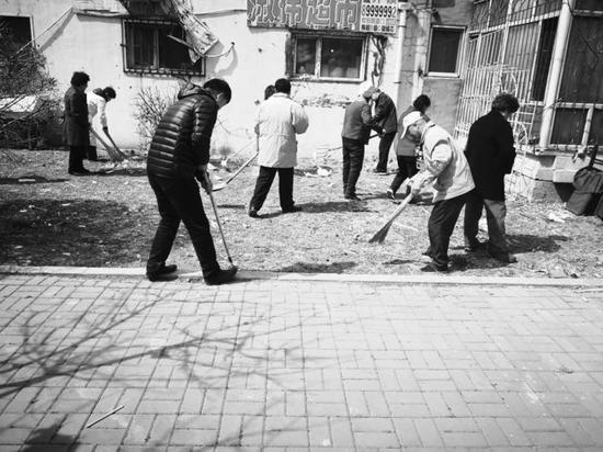 老年巡逻队成员清理野广告和小区垃圾。 袁迪 摄