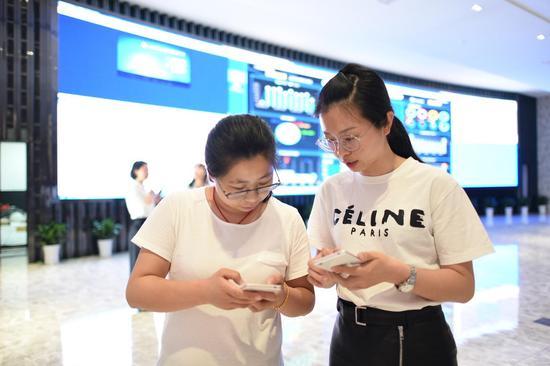 八角塘社区居委会杨宝丽(左)和西市街道办天津桥居委会 刘蓓芬(右)正在使用综治APP