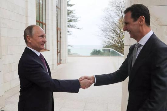 11月20日,在俄罗斯索契,俄罗斯总统普京(左)与叙利亚总统阿萨德握手。新华社/美联