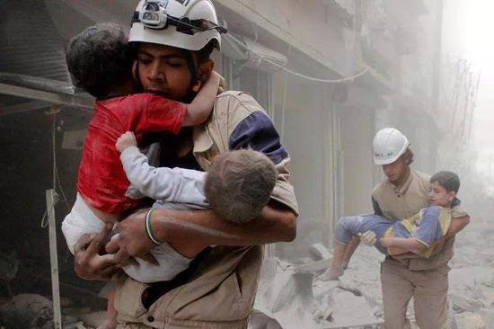 一位父亲拎着他被炸死的儿子绝望的跑向医院。