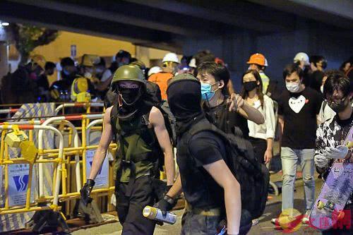 杨逸朗(左)在警总门外上齐装备准备对警总进行冲击。(图源:文汇报)