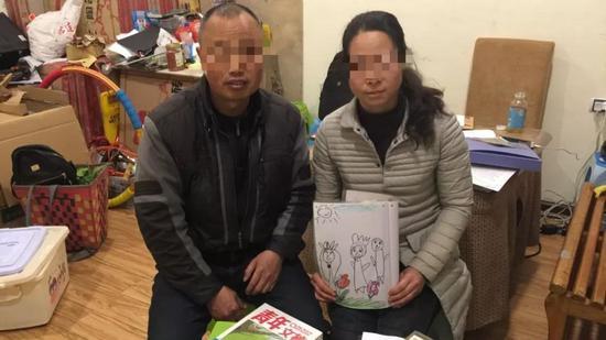 """2019年3月17日,陈浩瀚父母准备了一箱书籍,计划第二天探视时送给陈浩瀚,陈妈妈手中捧着儿子幼儿园时画的""""一家三口""""。 新京报记者 韩茹雪 摄"""