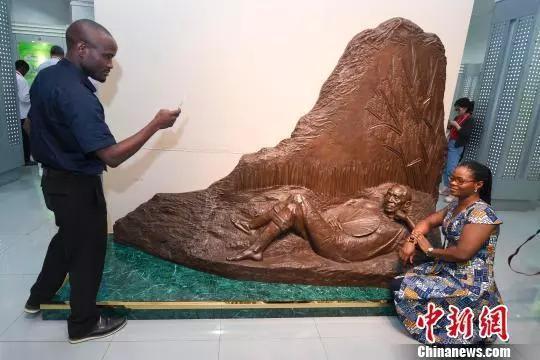 """非洲记者在""""禾下乘凉""""雕塑前留影。"""