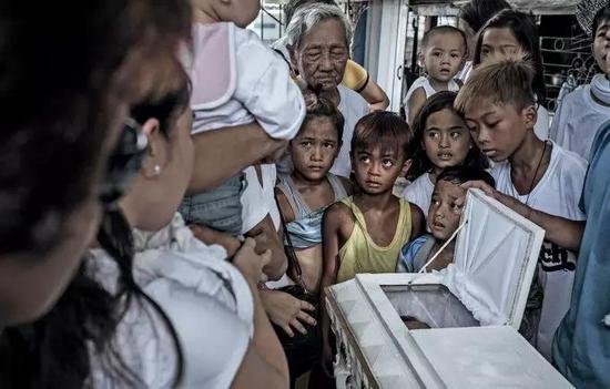 定居于此的幼孩子们正在不雅旁观一场葬礼