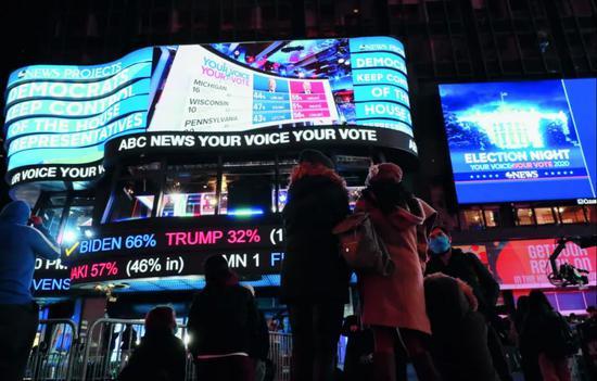 11月3日,人们在美国纽约时报广场不雅旁观2020年美国大选实时计票效果。图/新华