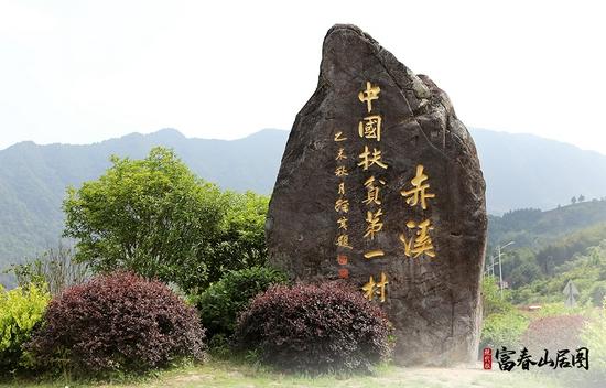 """村口矗立的""""中国扶贫第一村""""石碑。"""