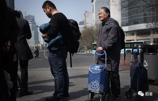 严敏文从望京西里先后乘坐421路和57路到广安门内。在广安门内公交车站,她背着背包、拿着两个小推车站在等车人群之间,准备乘坐公交917快前往涞水县。新京报记者尹亚飞摄