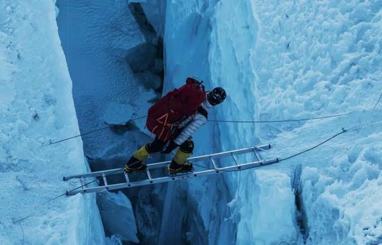 5月24日,登山者正在跨越昆布冰川的梯子,其下面是几十米的冰裂缝。摄影/Rocker