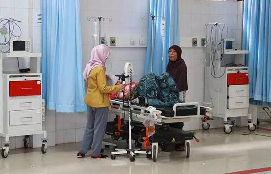 12月26日,在印度尼西亚万丹省板底兰县贝尔卡医院,在海啸中受伤的居民批准治疗。(新华社记者张可任摄)