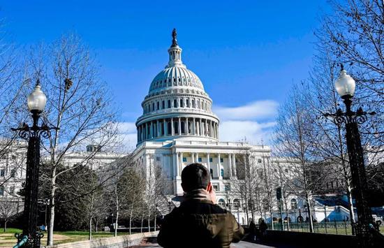 2018年12月22日,在美国华盛顿,一名游客站在国会大厦外。新华社/法新