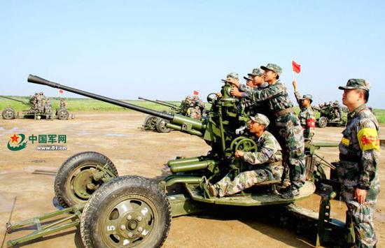 穿着07式夏迷彩作训服的预备役官兵进行高炮射击训练。