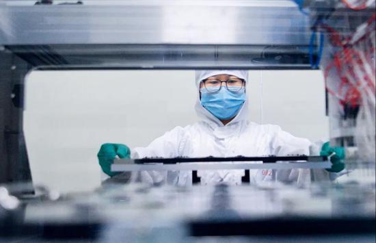 四川成都的一家生物公司内,洁净车间工作人员将可检测新冠病毒的核酸检测试剂盒芯片送进印制机器。图/中新