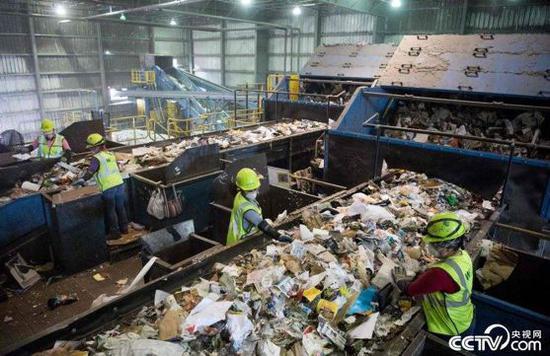 (图为垃圾分类线上的美国工人们 图源:央视网)