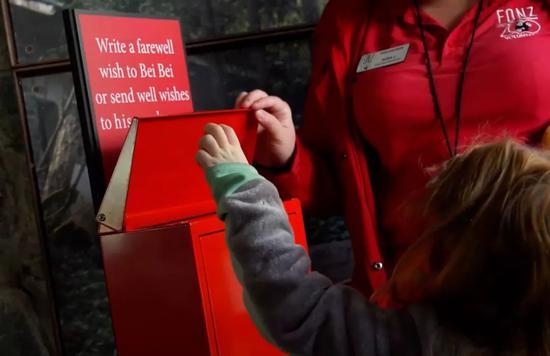 ▲一個孩子將祝福卡片投入信箱。(視頻截圖)