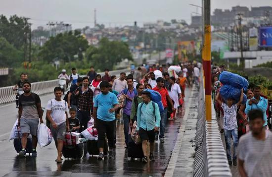 8月4日,印度当局宣布在印控克什米尔实行军管,并切断互联网,在当地的游客被迫步行至火车站(来源:美联社)