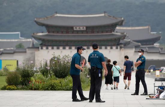 8月16日,警察在韩国首尔戴口罩执勤。新华社/美联