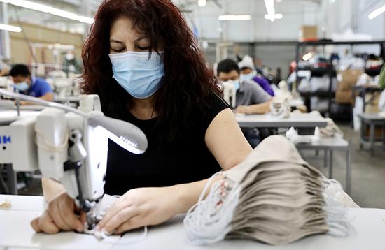 2020年4月16日,在美国洛杉矶的一家工厂内,工人们在缝制口罩。图|新华社