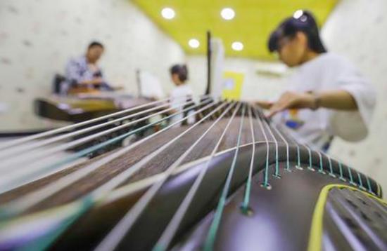▲一学生在课外兴趣班上练习古筝弹奏。图片来源:新华社