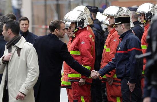"""当地时间2018年12月2日,法国巴黎,法国总统马克龙走访前一日发生暴力冲突的街道。1日""""黄背心""""示威者在巴黎市中心与防暴警察发生激烈冲突,反政府抗议者点燃了数十辆汽车,数千人参加了反对高燃油税的""""黄背心""""抗议活动。 视觉中国 图"""