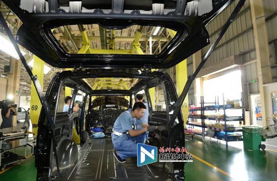福建奔驰生产车间内,工人正在忙碌。叶义斌/摄