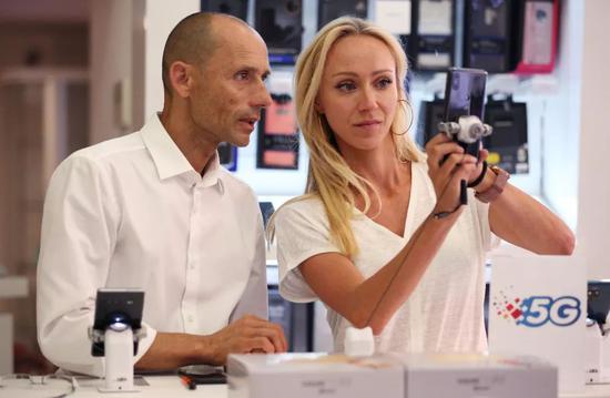 7月23日,在摩纳哥电信公司的营业厅里,当地居民亚历克斯(左)向销售人员咨询5G手机和业务。新华社记者高静摄