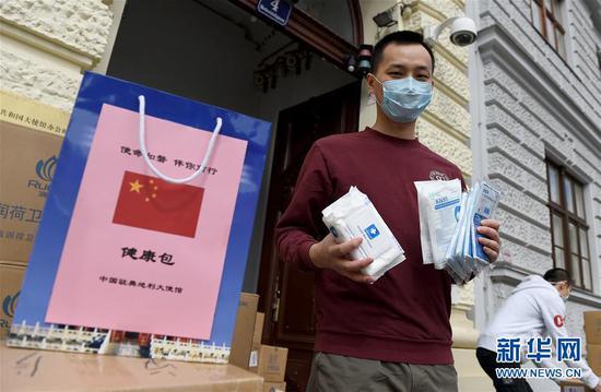 """4月17日,在奥地利首都维也纳的中国驻奥地利大使馆前,中国留学生吕荟展示使馆发放的""""健康包""""内的防疫物品。 新华社记者 郭晨 摄"""