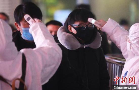 资料图:防疫人员正在给旅客检测体温。泱波 摄