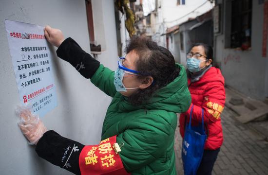 2月7日,在离武汉著名景点黄鹤楼不远的中华路街道西城壕社区,社区网格员曹岚英(左)在张贴防疫提示。新华社记者 肖艺九 摄
