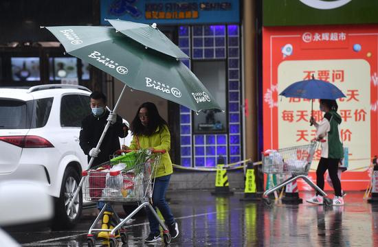 10月6日,在北京通州一家超市,工作人员撑起太阳伞,为没带伞的顾客遮雨。